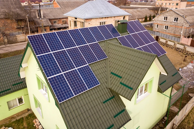 Aerial view of  house cottage with blue shiny solar photo voltaic panels system on the roof. renewable ecological green energy production concept.