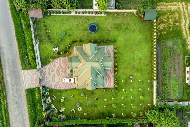 Aerial view of house shingle roof and a car on paved yard with green grass lawn.