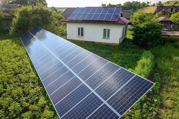 Aerial view of a house with blue solar panels for clean energy.