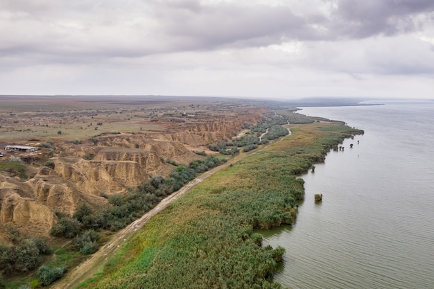 Aerial view at huge lake with beautiful sand dunes and green shore and early evening sky