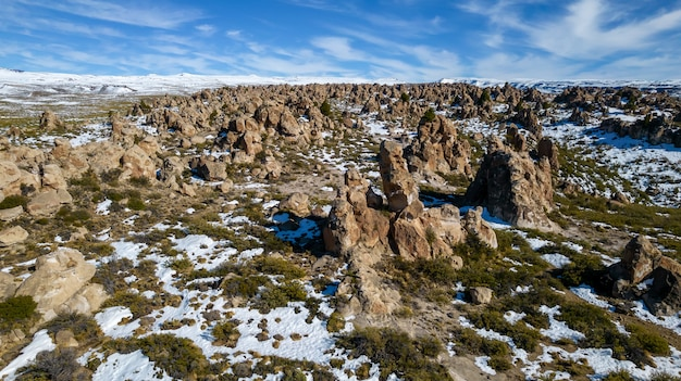 Aerial view of ignimbrite rock field with snow. in the andes mountain range.