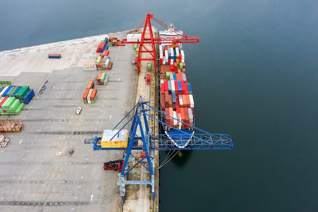 Aerial view of an industrial cargo ship with containers for loading at a seaport, shot from a drone