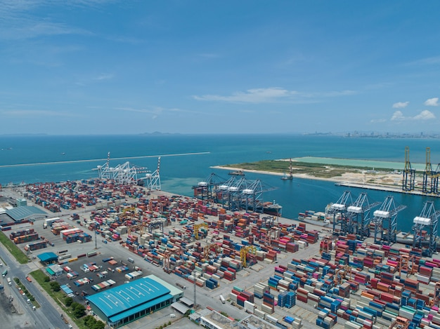 Aerial view of industrial port with containers, large container vessel unloaded in port.