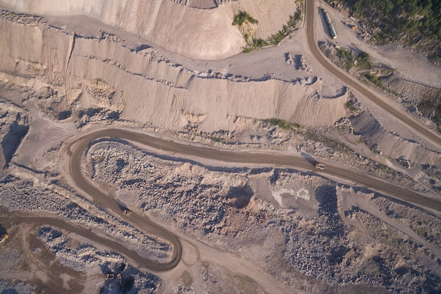 Aerial view of industrial truck moves along the road in the sand quarry.