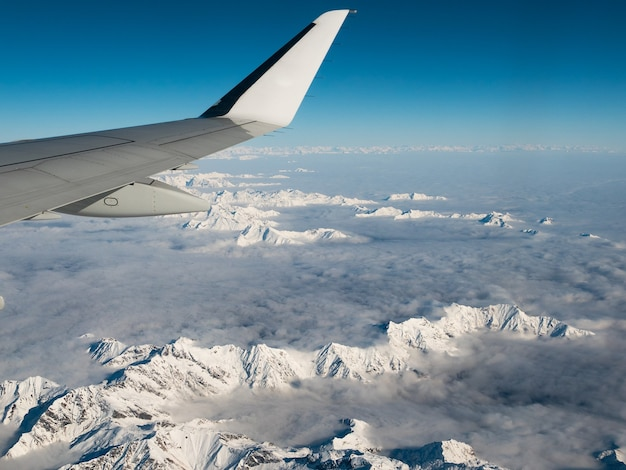 Aerial view of the italian swiss alps in winter, with generic aeroplane wing.