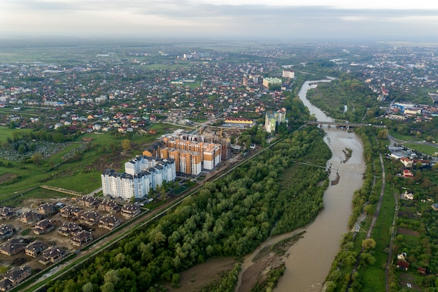 Aerial view of ivano-frankivsk city with residential area and suburb houses with river in middle.