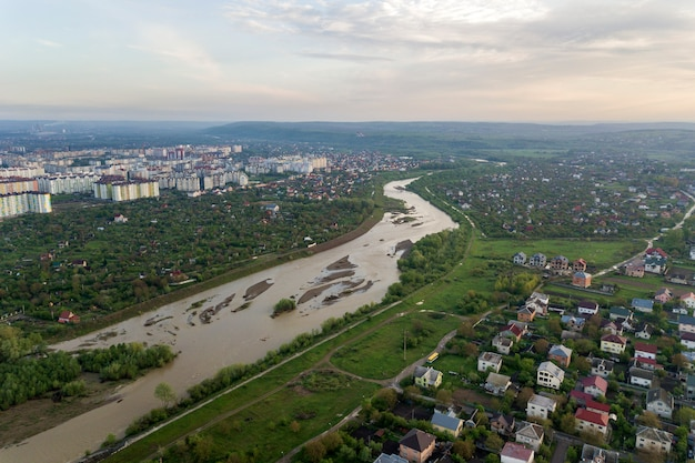 Aerial view of ivano-frankivsk city with residential area and suburb houses with a river in middle.