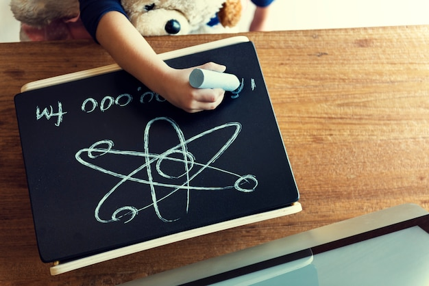 Aerial view of kid hand drawing on chalkboard