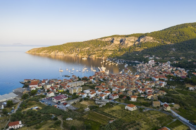 Aerial view of komiza town on vis island, croatia in dalmatia at sunrise. city laying on seaside in mediterranean sea surrounded by hills in summer vacation season.