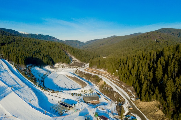 Aerial view of landscape of ski and snowboard slopes through pine trees going down to winter resort in carpathians