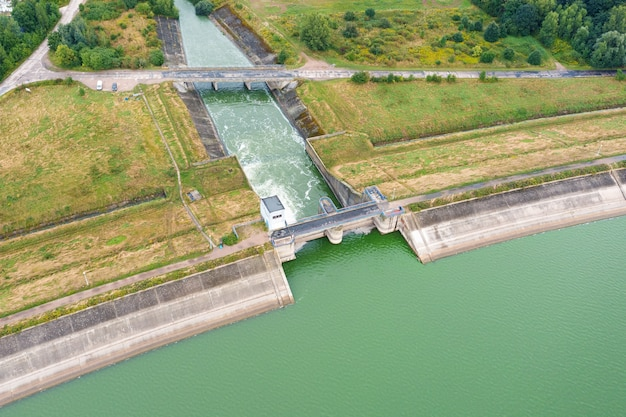 Aerial view of a large dam with a strong stream of water on the lake, in the city of metkow poland
