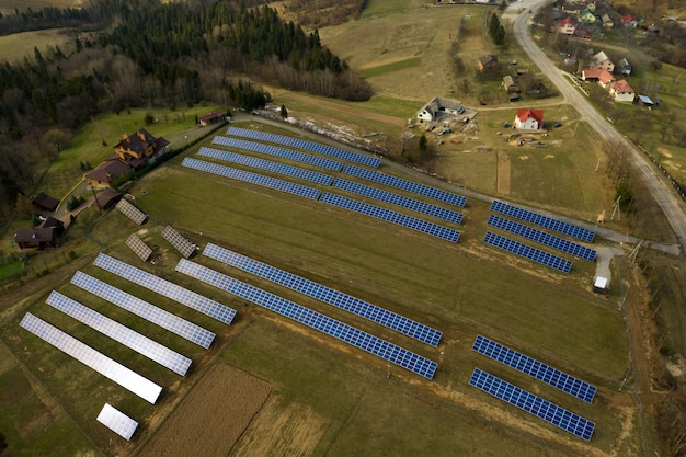 Aerial view of large field of solar photo voltaic panels system producing renewable clean energy on green grass background.