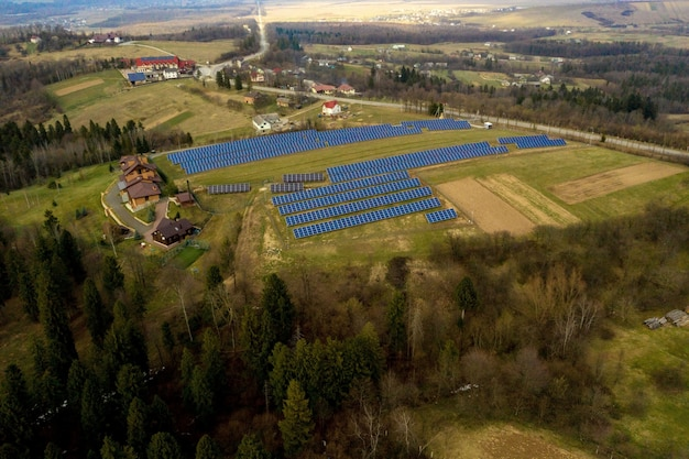 Aerial view of large field of solar photo voltaic panels system producing renewable clean energy on green grass