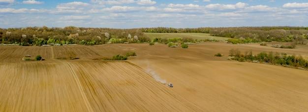 Вид с воздуха на большой трактор, обрабатывающий сухое поле. сверху вниз трактор с высоты птичьего полета обрабатывает землю и засевает сухое поле. воздушный трактор прорезает борозды на сельскохозяйственных полях для посева.