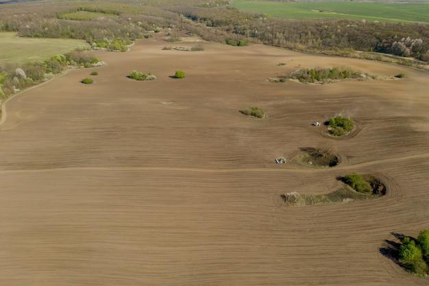 Вид с воздуха на большой трактор, возделывающий сухое поле. сверху вниз трактор с высоты птичьего полета обрабатывает землю и засевает сухое поле. воздушный трактор прорезает борозды на сельскохозяйственных полях для посева.