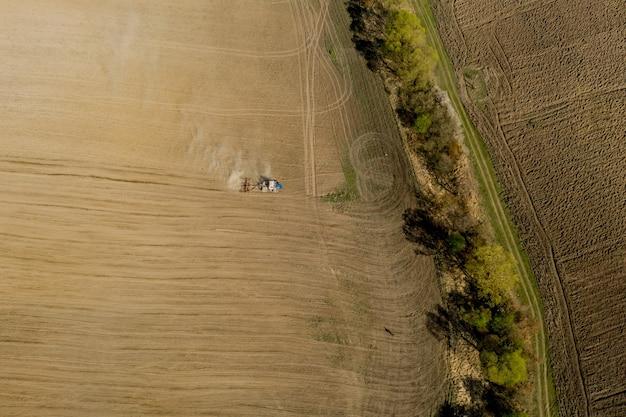 Вид с воздуха на большой трактор, возделывающий сухое поле. сверху вниз трактор с высоты птичьего полета обрабатывает землю и засевает сухое поле.