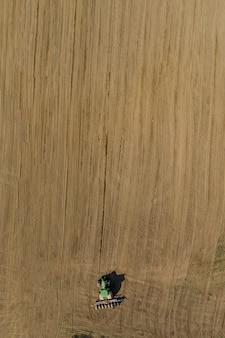 Вид с воздуха на большой трактор, возделывающий сухое поле.