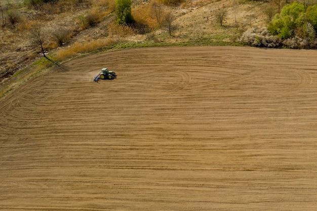 ドライフィールドを耕作する大型トラクターの空中写真。
