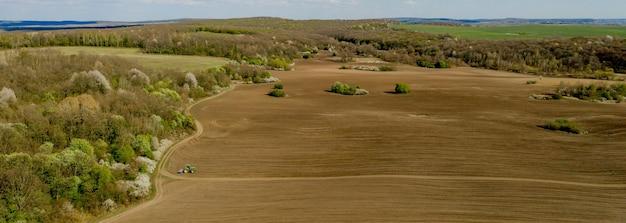 Вид с воздуха на большой трактор, возделывающий сухое поле