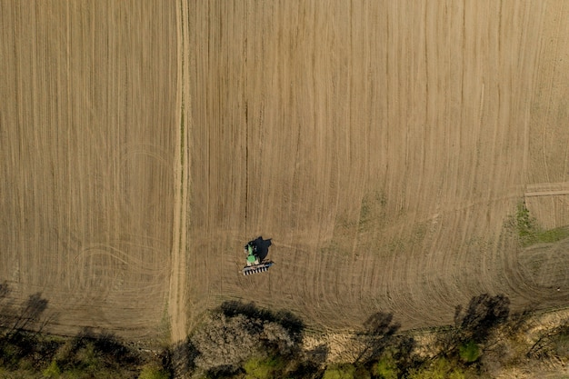 Aerial view large tractor cultivating a dry field. top down aerial view tractor cultivating ground and seeding a dry field. aerial tractor cuts furrows in farm field for sowing.