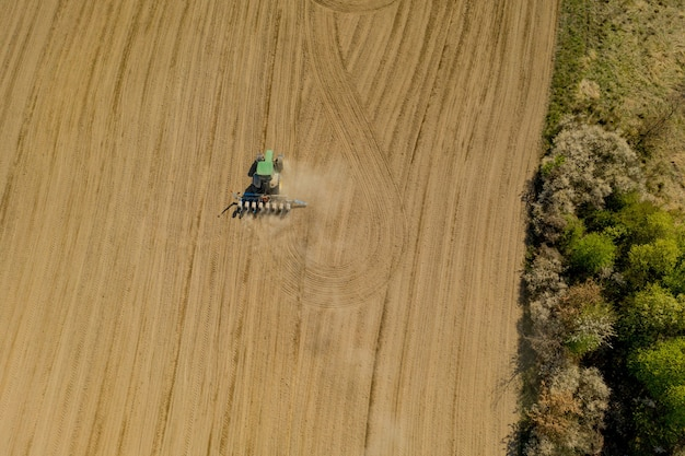 Aerial view large tractor cultivating a dry field.
