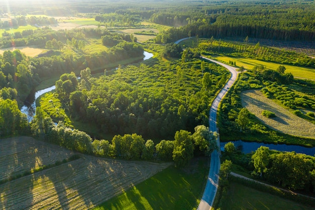 Aerial view of latvian rural landscape with a winding river, forests and country roads at sunset