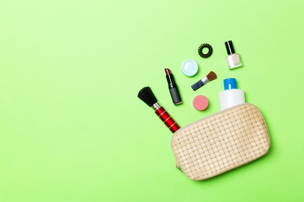 Aerial view of a leather cosmetics bag with make up beauty products spilling out on green background