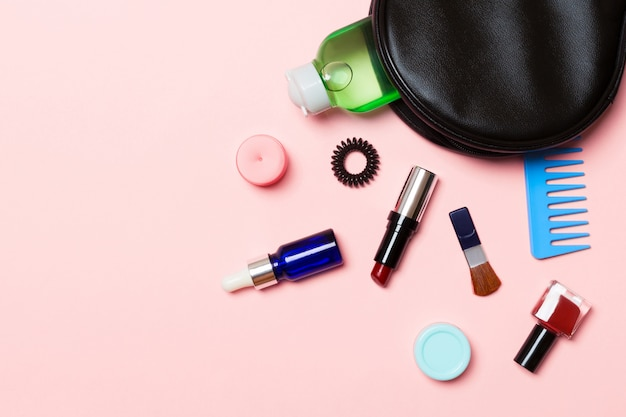 Aerial view of a leather cosmetics bag with make up beauty products spilling out on pink