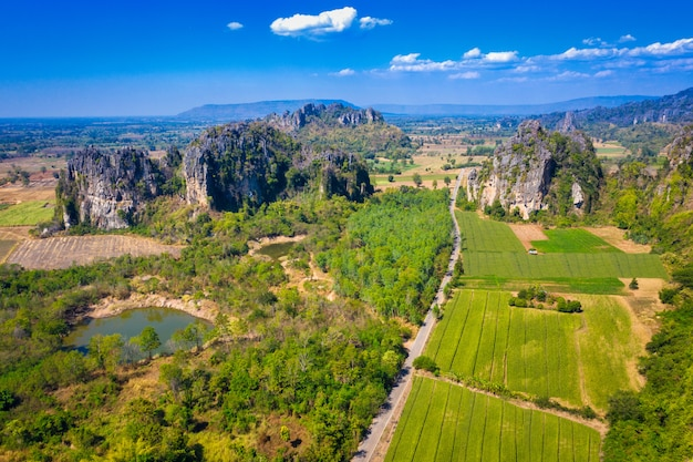 Aerial view of limestone mountain and rice field in noen maprang district, phitsanulok, thailand.