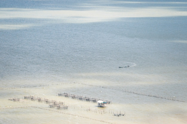 Aerial view of local fishing boat and traditional fish trap with wooden floating house in the songkhla lake. thailand.