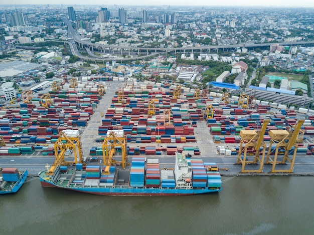 Aerial view of logistics and transportation of container cargo ship and crane bridge