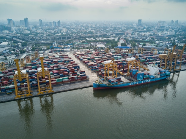 Aerial view of logistics and transportation of container cargo ship and crane bridge