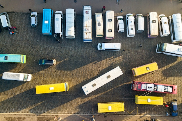 Aerial view of many cars and buses moving on a busy city street.
