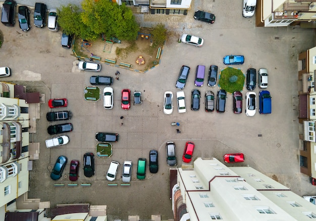 Aerial view of many colorful cars parked on public parking lot.