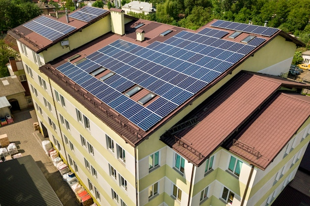 Aerial view of many solar panels on building roof.