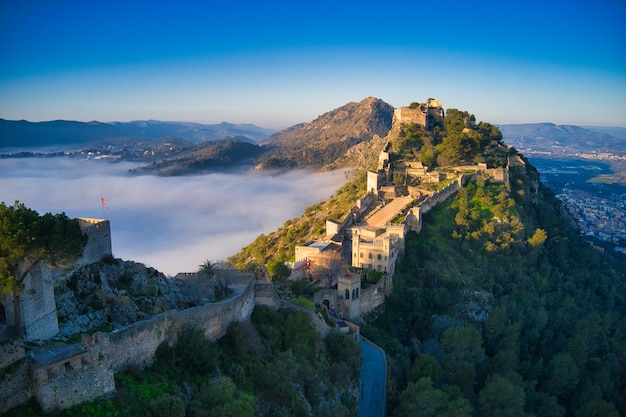 Aerial view of a medieval castle on a hill beautifully covered with fog