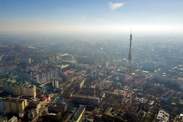Aerial view of modern city urban foggy landscape with tall television tower on bright blue sky copy space at dawn. drone photography.