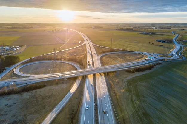 Aerial view of modern highway road intersection at dawn on rural landscape and raising sun background. drone photography.