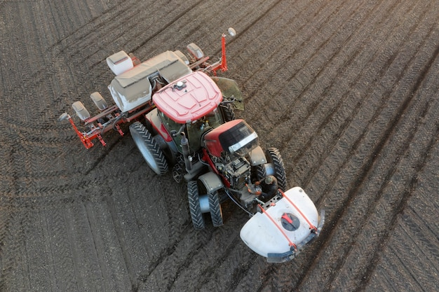 Aerial view of a modern multifunctional tractor, fertilizing pesticides, herbicides and sowing the area at the same time.
