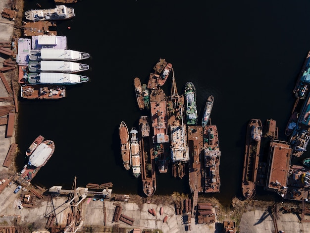 Aerial view of moored old barges and ships in river port