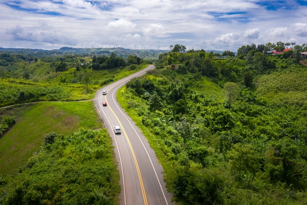 Aerial view over mountain road going through tropical rainforest landscape in thailand.