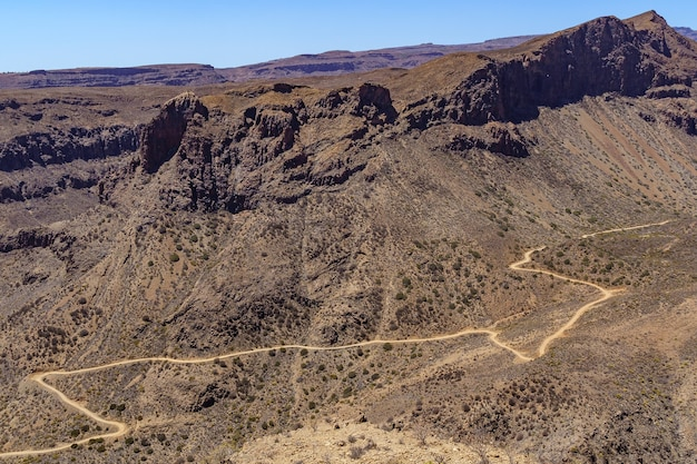 Aerial view of the mountains of gran canaria with a road that goes around the hillside making curves. spain. europe.