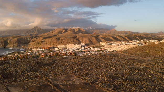 Aerial view of mountains and marine coast, village of houses, dry terrain and trails, canary islands