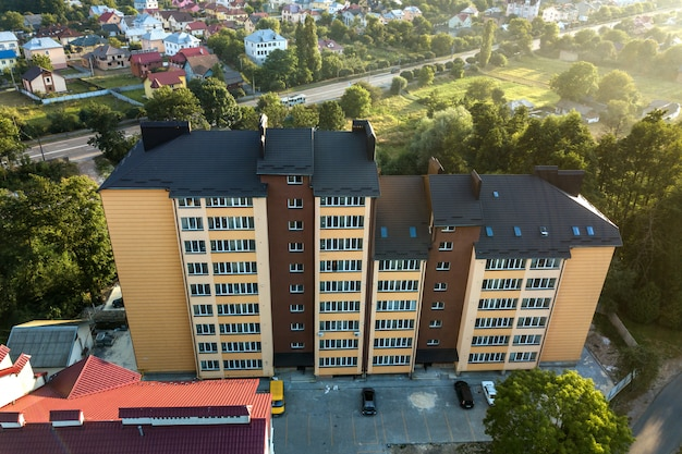 Aerial view of multistory apartment buildings in green residential area.