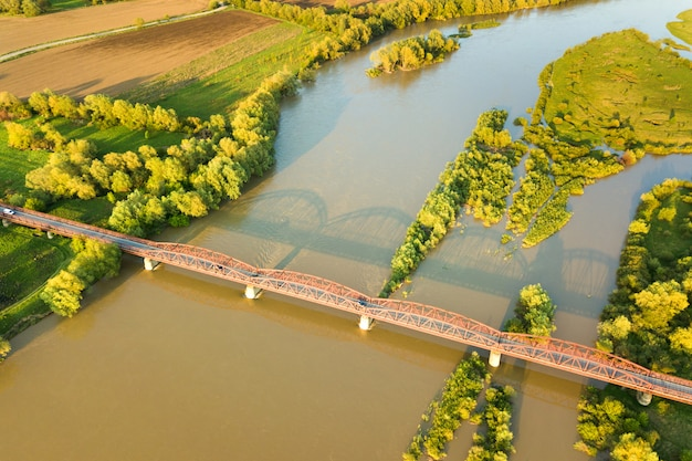 Aerial view of a narrow road bridge stretching over muddy wide river in green rural area.