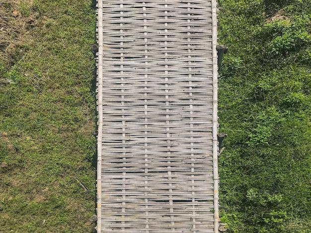 Aerial view of natural bamboo weave bridge way above grass field garden.