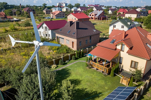 Aerial view of a new autonomous house with solar panels, water heating radiators on the roof and wind powered turbine on green yard.