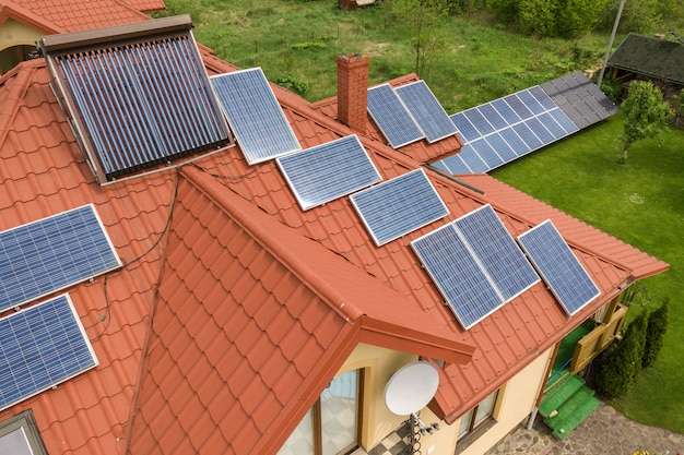 Aerial view of a new autonomous house with solar panels and water heating radiators on the roof.