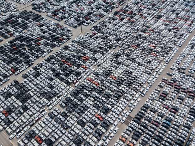Aerial view of new cars parked at the parking area of automobile factory. w
