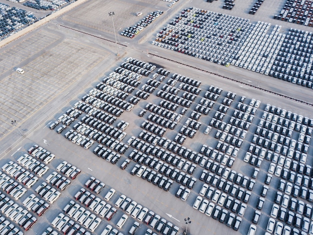 Aerial view of new cars parked at the parking area of automobile factory.